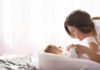 Mother with her newborn son lay on the bed in the rays of sunlight coming out of the window